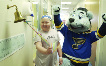 A young girl ringing a bell next to the St. Louis Blues' hockey mascot, a polar bear in a blue jersey.