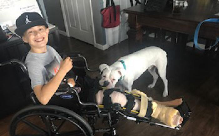 Ashton is comforted by his dog following surgery to repair injuries sustained in a boating accident.